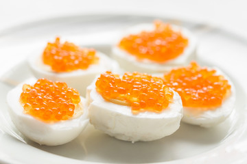 Boiled egg with red caviar a culinary dish
