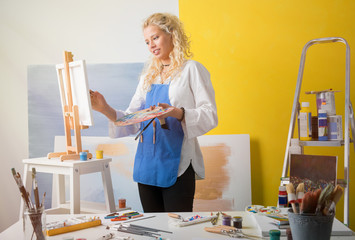 Woman in studio painting an artistic  picture