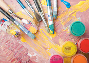 Artist paint brushes and color containers on colorful background