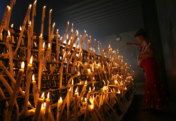 A pilgrim lights candles in the shrine of El Rocio in Almonte in the province of Huelva