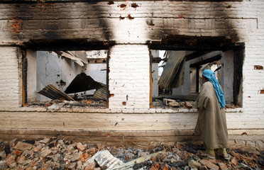Kashmiri woman assesses damage to a house after gun battle in Chinad
