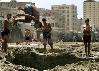 CUBAN BOY DIVES INTO A SMALL POOL CARVED ON THE FAMOUS MALECON SEAFRONT IN HAVANA.