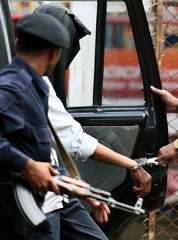 Police escort a suspect arrested in connection with the recent bomb blasts in Mumbai