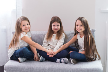 Portrait of three happy girls sitting on sofa and friendship concept