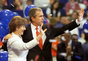 George W. Bush and his wife Laura wave as balloons drop on stage after he was nominated as the Repub..