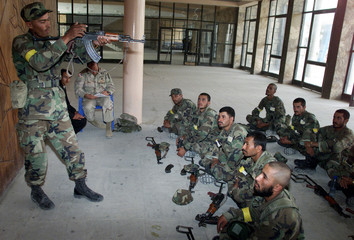 AN AFGHAN ARMY STUDENT SHOW HIS SKILLS WITH AK47 IN KABUL.