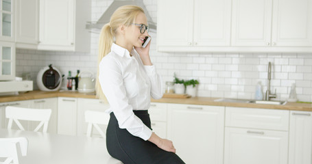 Wonderful young smiling blonde in formal clothing sitting on table at modern kitchen and talking by phone.