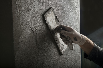 Hand of a construction worker plastering and smoothing concrete wall close-up.