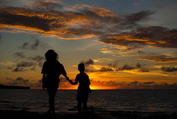 Mom and son at sunset by the ocean.