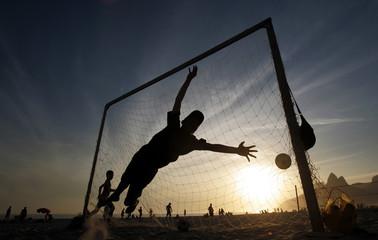 Brazilian kids play soccer at sunset on Ipanema beach in Rio de Janeiro.