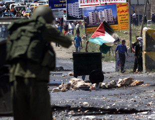 ISRAELI SOLDIER TAKES AIM AT PALESTINIAN WITH FLAG IN RAMALLAH CLASHES.