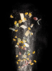 Ingredients for Italian kitchen (tomato, pasta, cheese, chopping board and knife) isolated in the air on black background, freeze motion image