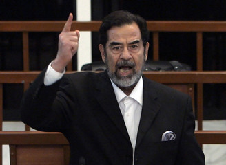 Former Iraqi president Saddam Hussein yells at the court as he receives his verdict during his trial in Baghdad