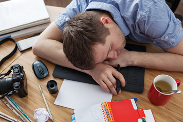 The designer fell asleep in the workplace from fatigue. Process photos or draw sketches on the tablet.