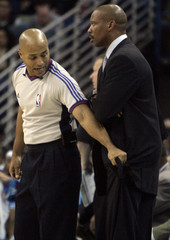 New Orleans Hornets head coach Byron Scott is held back by official Mark Davis against the New York Knicks in New Orleans