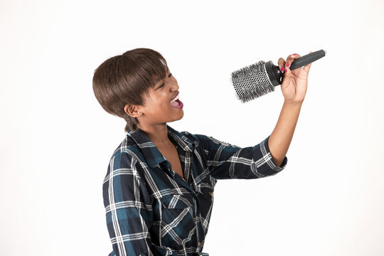 Attractive african female using a hair brush as an microphone
