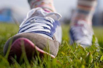 The girl is walking along the green grass in sneakers. Spring walk in the park