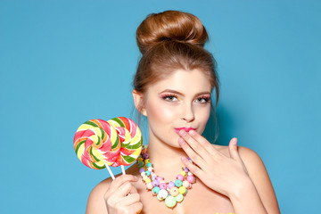 Portrait of a beautiful young woman with candy on a blue background. The blonde with the colored candy. Sweet. Woman with bright