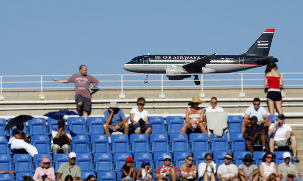 A U.S. Airways aeroplane lands in the background of Aurther Ashe stadium during the U.S. Open tennis tournament in Flushing Meadows in New York