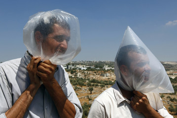 Palestinian protesters use plastic bags to avoid tear gas fired by Israeli soldiers during a protest against the controversial Israeli barrier in the West Bank village of Bilin