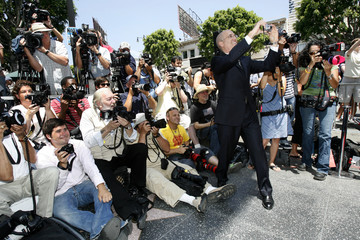Jeffrey Katzenberg, CEO of Dreamworks Animation, takes a photograph of television producer Mark Burnett (not pictured) as he stands on his star on the Walk of Fame in Hollywood