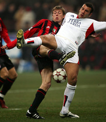 AC Milan's Tomasson challenges Loria of Cagliari during their Serie A match in Milan.