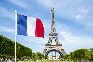 French flag flying in bright blue sky above the Eiffel Tower in Paris, France Fotomurales