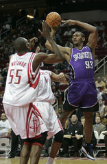 Kings forward Artest passes from under basket past Rockets center Mutombo during NBA game in Houston