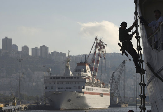 Trainee climbs a rope ladder costumed as pirate during an anti-piracy drill at the port of Haifa