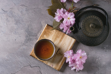 Black iron teapot and traditional ceramic cup of tea on wooden serving board with blossom pink flowers cherry branch over gray texture background. Top view with space, Asian style.