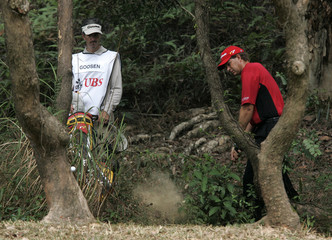 South Africa's Goosen hits from bush during 4th hole at Hong Kong Open golf tournament