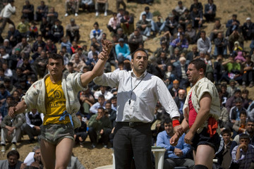 A judge holds up the hand of a wrestler to announce him as the winner after a traditional wrestling match in the village of Fariman