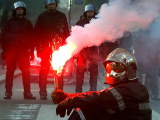 A French firefighter holds a red flare in front of riot police during a protest in Lille with around..