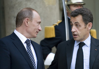 France's President Sarkozy speaks with Russia's Prime Minister Putin in Paris