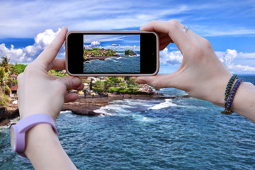 A woman photographs the beautiful sea landscape . Close-up of hands.