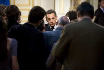 France's President Sarkozy speaks with journalists after delivering a speech in Paris