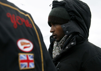 An Eritrean asylum seeker waits for a meal during a daily midday food distribution service near the harbour of Calais