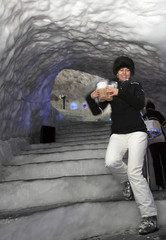 Monika Gamper walks down stairs of ice carrying hot drinks before a performance by Norwegian musician Terje Isungset, in the valley of Val Senales