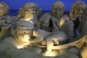 A couple takes a picture with sand figures depicting the nativity scene as part of Christmas celebrations, at La Pineda beach in Salou