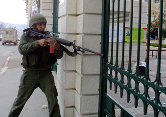 ISRAELI SOLDIER GUARDS THE ENTRANCE TO THE BETHLEHEM UNIVERSITY.