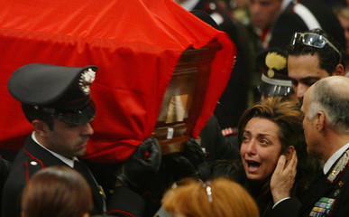 A WOMAN IS OVERCOME WITH GRIEF AS SHE APPROACHES THE COFFIN OF HERLOVED ONE.