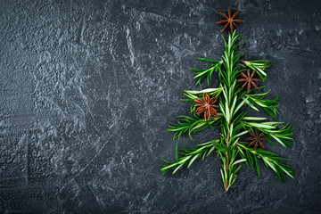 Christmas tree of rosemary and anise on a black plate background. Selective focus.Top view. Place for text.