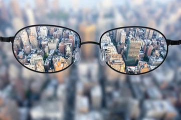 Clear cityscape focused in glasses lenses Wall mural