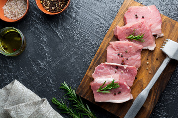Meat. Raw pieces of pork with rosemary and pepper on a black background. Selective focus. Top view. Place for text.