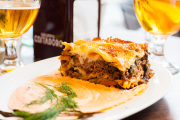 Lasagne food on the table. Glass of beer in background