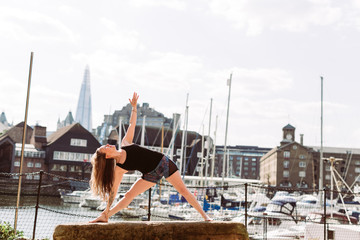 Woman in Yoga position at harbour