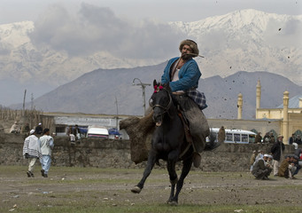 Afghan horseman carries the carcass during a Buzkashi game in Kabul