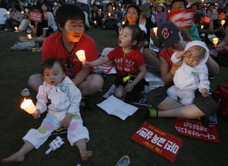 People participate in a candle-light rally to demand full-scale renegotiation of a beef deal with the U.S. and the resignation of President Lee Myung-bak in central Seoul