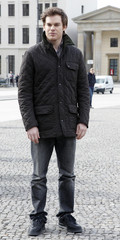 """Actor Hall poses for media in front of Brandenburger gate to promote his television series """"Dexter"""" in Berlin"""