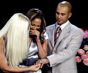 SINGER JENNIFER LOPEZ AND HER HUSBAND SHOW THEIR WEDDING RING TODESIGNER DONATELLA VERSACE.